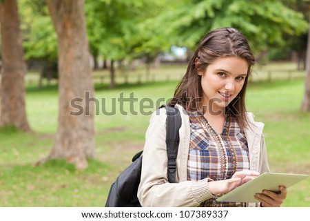 Portrait of a first-year female student using a touch pad in a park - stock photo