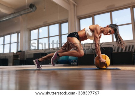 Portrait of a fit and muscular woman doing intense core workout with kettlebell in gym. Female exercising at crossfit gym. - stock photo