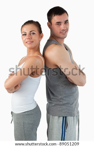 Portrait of a fit couple posing against a white background - stock photo