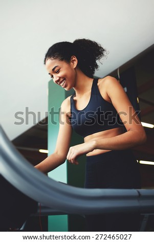 Portrait of a fit ethnic woman with curly hair using a treadmill at gym - stock photo