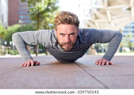 Portrait of a fit man doing push ups outdoors - stock photo