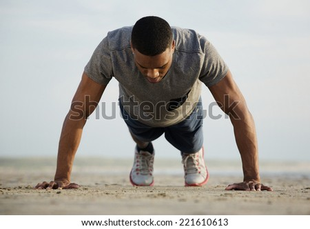 Portrait of a fit young man doing push ups at the beach - stock photo