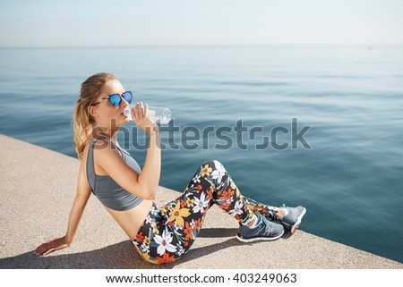 Portrait of a fit young woman resting after successful jogging workout outdoors. Pretty athlete blond wearing sportswear and sunglasses drinking water while sitting on beach during physical training - stock photo