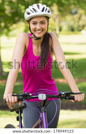 Portrait of a fit young woman with helmet riding bicycle at the park - stock photo