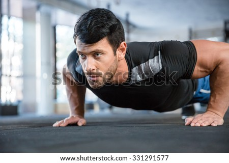 Portrait of a fitness man doing push ups in gym - stock photo