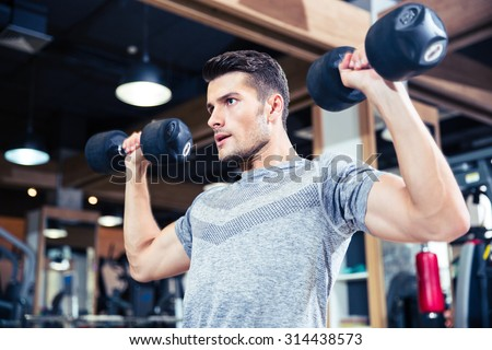 Portrait of a fitness man workout with dumbbells at gym - stock photo