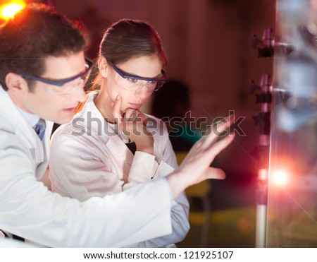 Portrait of a focused electrical engineering researchers in their working environment checking the phenomenon of breaking laser beam on the glass surface. - stock photo