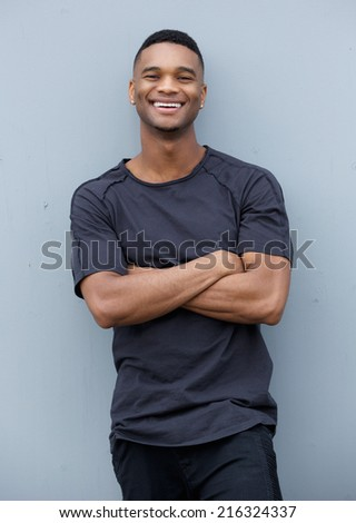 Portrait of a friendly black man smiling with arms crossed against gray background  - stock photo