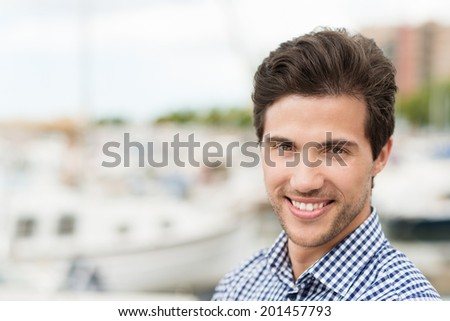 Portrait of a friendly handsome unshaven young man with a lovely warm smile against a marine harbour with shallow dof and copyspace - stock photo