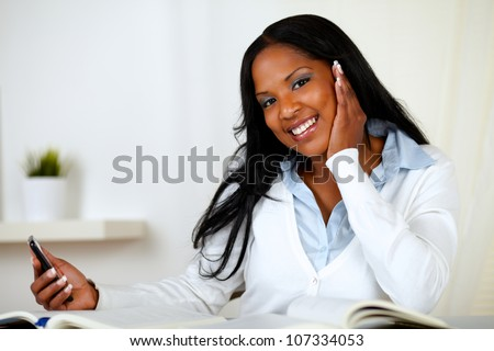 Portrait of a friendly young woman looking to you while holding a cellphone in one hand at home indoor - stock photo