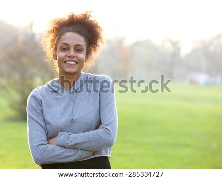 Portrait of a friendly young woman standing outside  - stock photo