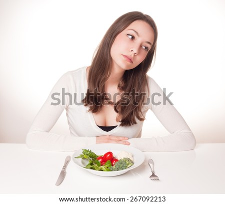 Portrait of a frustrated looking young brunette woman with plate of vegetables. - stock photo