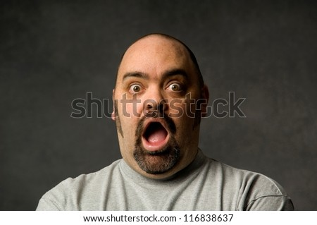 Portrait of a funny bald man with opened mouth - stock photo
