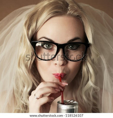 portrait of a funny beautiful hipster bride drinking something from tin can through red plastic sipper. daylight. studio shot - stock photo