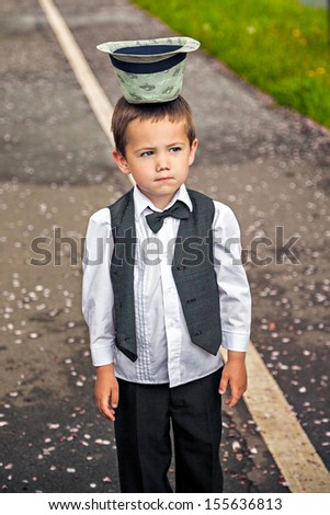Portrait of a funny boy in a waistcoat and hat upside-down outdoor - stock photo