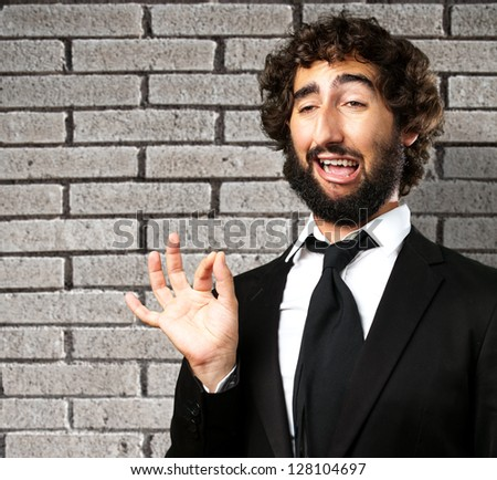 Portrait Of A Funny Businessman against a grey brick wall - stock photo