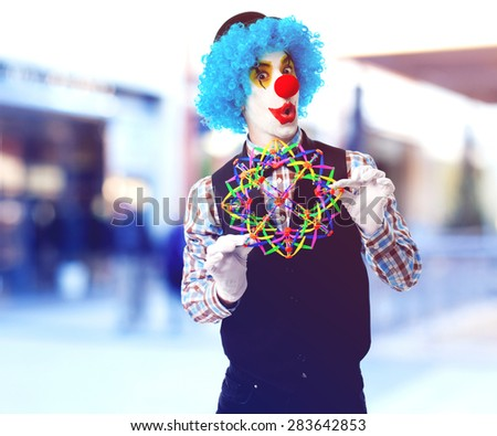 portrait of a funny clown playing with a toy ball - stock photo