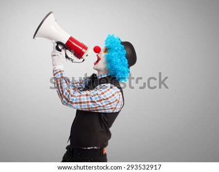 portrait of a funny clown shouting with a megaphone - stock photo