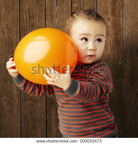 portrait of a funny kid holding a big orange balloon against a wooden background - stock photo
