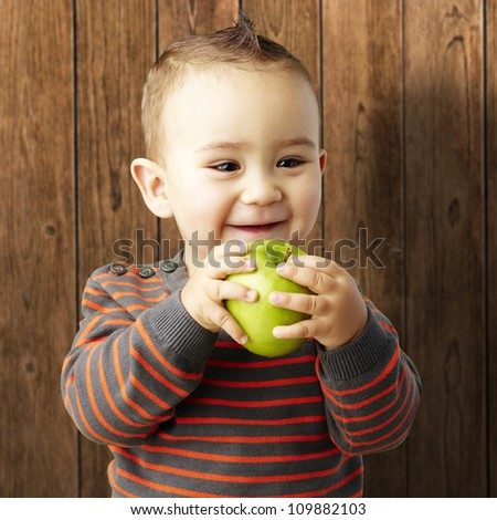 portrait of a funny kid holding a green apple and smiling against a wooden background - stock photo