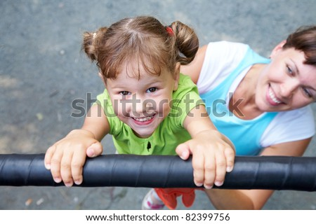 Portrait of a funny little girl hangs by horizontal bar with mother - stock photo