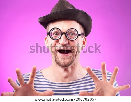 Portrait of a funny pervert nerd in hat touches imaginary boobs  - stock photo