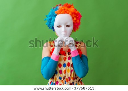 Portrait of a funny playful female clown in colorful wig holding a mask on her face, standing on a green background - stock photo