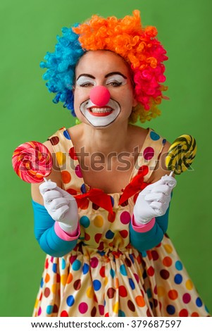 Portrait of a funny playful female clown in colorful wig holding lollipops in both hands and smiling, standing on a green background - stock photo