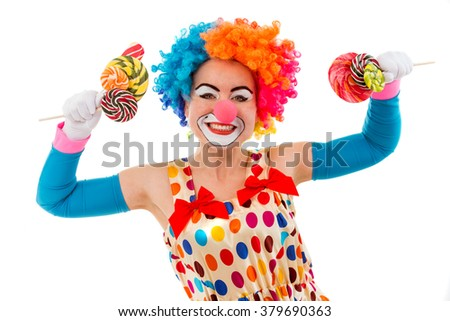 Portrait of a funny playful female clown in colorful wig holding lollipops in both hands, looking at camera and smiling, isolated on a white background - stock photo
