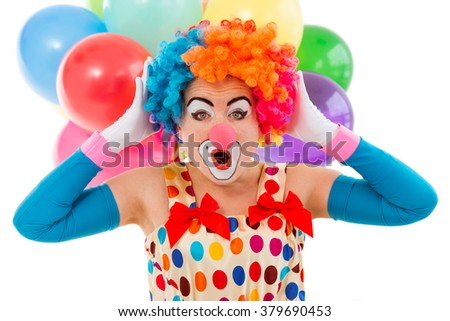 Portrait of a funny playful female clown in colorful wig keeping hands on head and showing emotions, in the background balloons, isolated on a white - stock photo