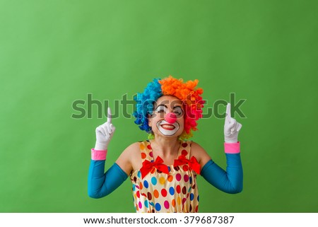 Portrait of a funny playful female clown in colorful wig pointing and looking upward and smiling, standing on a green background - stock photo