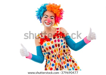 Portrait of a funny playful female clown in colorful wig showing OK sign, looking at camera and smiling, isolated on a white background - stock photo