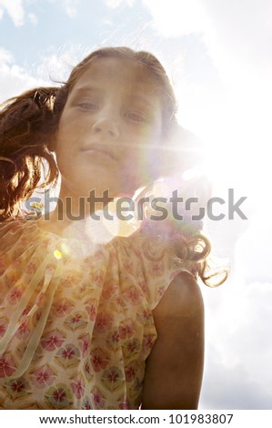 Portrait of a girl against the blue sky with sun rays and flare coming through. - stock photo