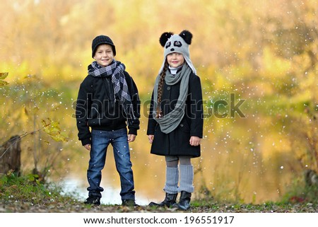 Portrait of a girl and boy in autumn - stock photo