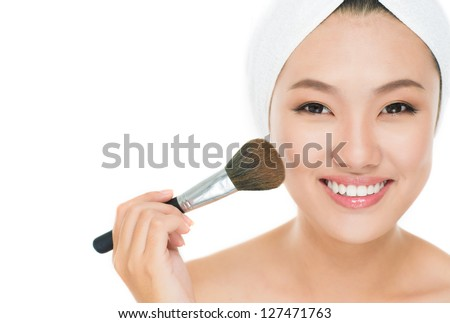 Portrait of a girl applying blusher on her cheeks - stock photo