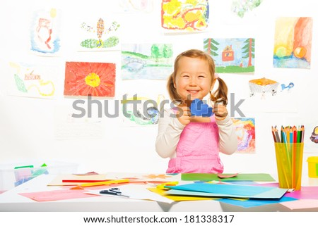 Portrait of a girl holding blue paper cloud and smiling - stock photo
