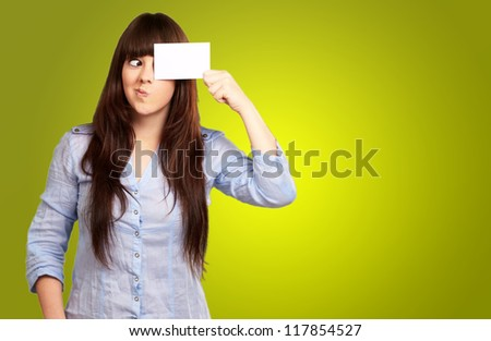 Portrait Of A Girl Holding Paper And Making Face On Green Background - stock photo