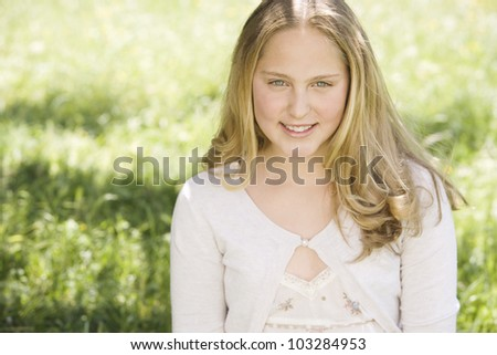Portrait of a girl in a field of green grass, smiling under a golden light. - stock photo