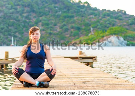 portrait of a girl in a lotus position on the pier  - stock photo