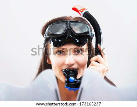 Portrait of a girl in snorkeling gear on light background - stock photo