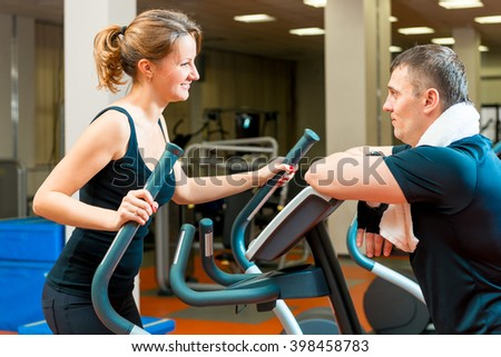 portrait of a girl in the gym and her trainer - stock photo