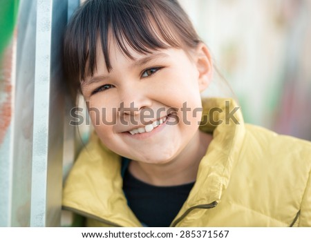 Portrait of a girl leaning to the wall, outdoor shoot - stock photo