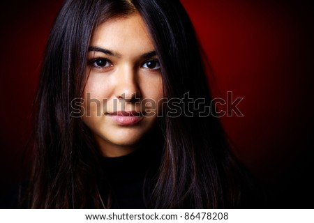 Portrait of a girl looking at camera in the dark - stock photo