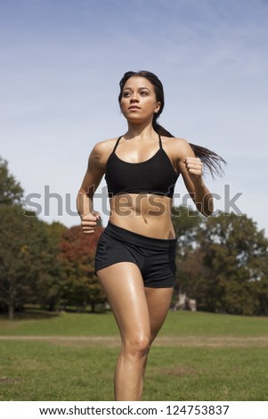 Portrait of a girl running in the park   background - stock photo