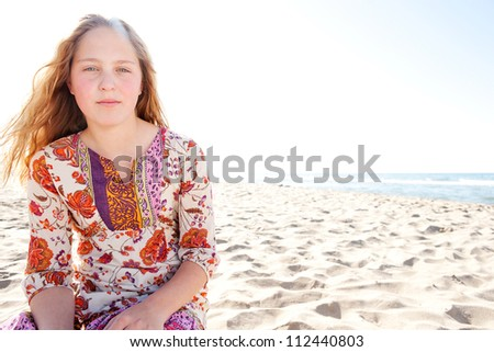 Portrait of a girl sitting down on a white sand beach wearing a floral dress with the sun in the sky. - stock photo