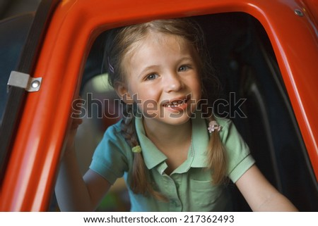 Portrait of a girl smiling in a toy helicopter - stock photo