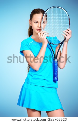 Portrait of a girl tennis player holding her racket. Studio shot. - stock photo