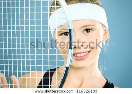 Portrait of a girl tennis player holding tennis racket. Studio shot. - stock photo