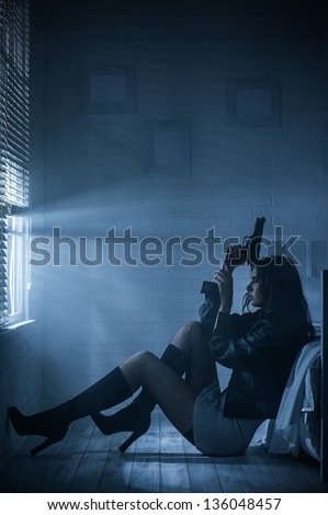 Portrait of a girl with a gun - stock photo