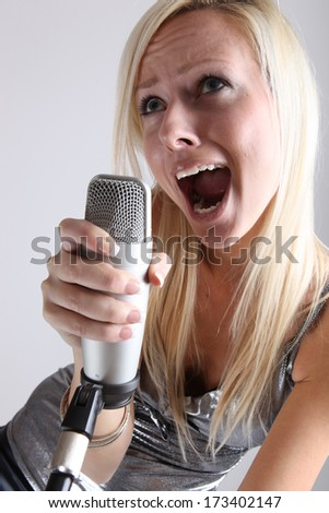 portrait of a girl with a microphone in the studio - stock photo